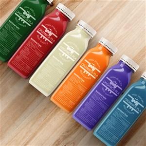 整齊排列在木紋背景上的七彩果汁瓶飲料瓶樣機