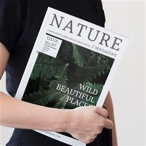 手夾著一本自然雜志樣機
