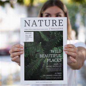 被女人拿在雙手上展示的自然雜志樣機
