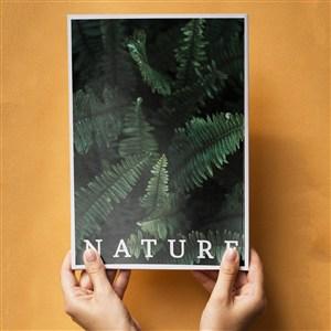 在橙色背景上手捧着一本自然杂志样机