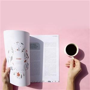 手拿咖啡杯正在翻阅杂志贴图样机