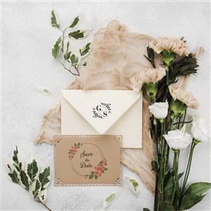 美丽的鲜花旁边的婚礼邀请函贴图样机