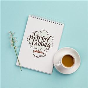 蓝色背景咖啡杯旁边的笔记本贴图样机