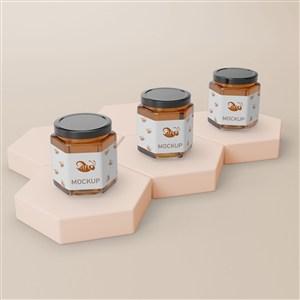3瓶放在六邊形展臺上的密封玻璃瓶蜂蜜包裝貼圖樣機