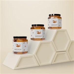 六邊形展臺上的3瓶密封玻璃瓶蜂蜜包裝貼圖樣機