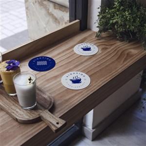 木质桌面上的3个蓝色杯垫隔热垫贴图样机