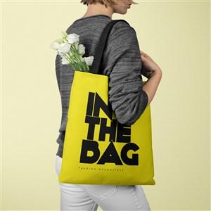 装着白色鲜花的黄色环保购物袋贴图样机