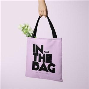 手拿装了鲜花的紫色环保购物袋贴图样机