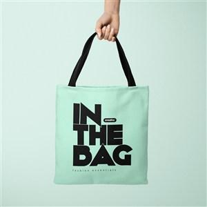 手拿绿色环保购物袋贴图样机
